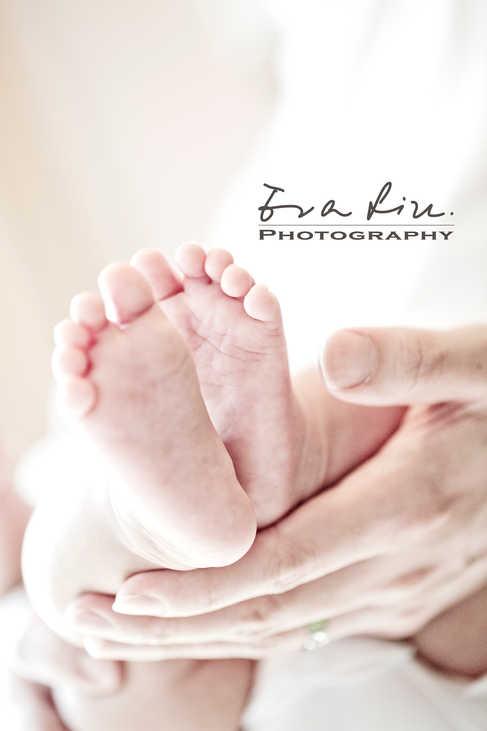 feet of newborn baby in daddy's hands