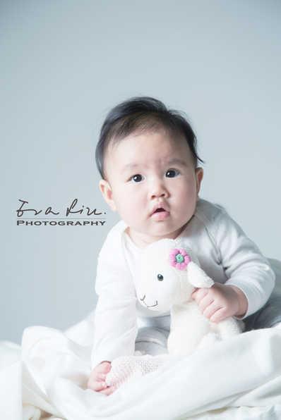 baby holding lamb plush