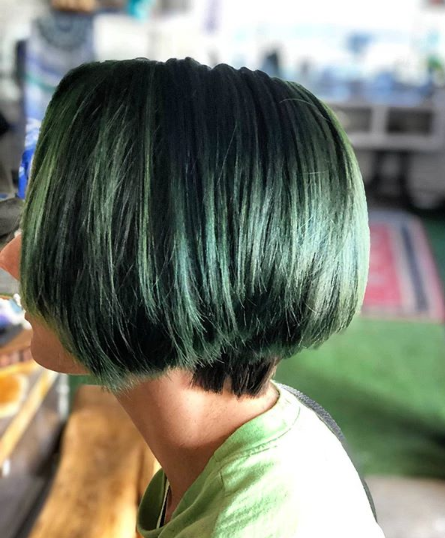 Undercut on her sides to a number 3 guard, 7+ inches off everything else and turned her to a lovely custom forest green. Came in originally booked for red and a cut and told me green when she came in.