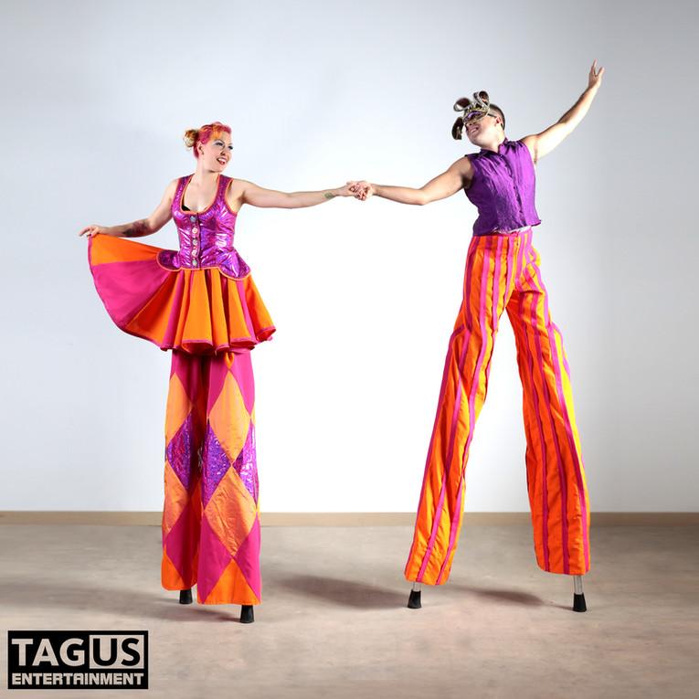 A lovely fushia and orange stiltwalking duo