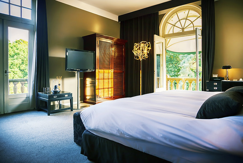 a modern hotel room with bed, tv, armoire, lamps, large open windows with sunlight streaming in