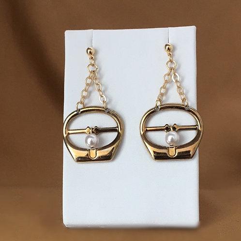 Dangle gold buckle earrings.