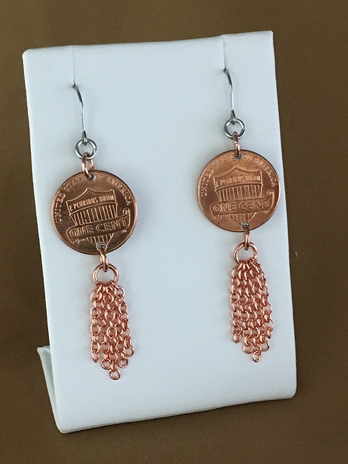 Thick fringed penny shield earrings.