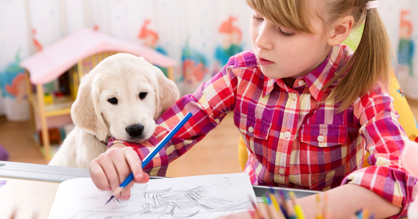 Cute girl drawing with her puppy.