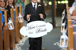 Here comes the bride sign held by ring bearer at wedding ceremony