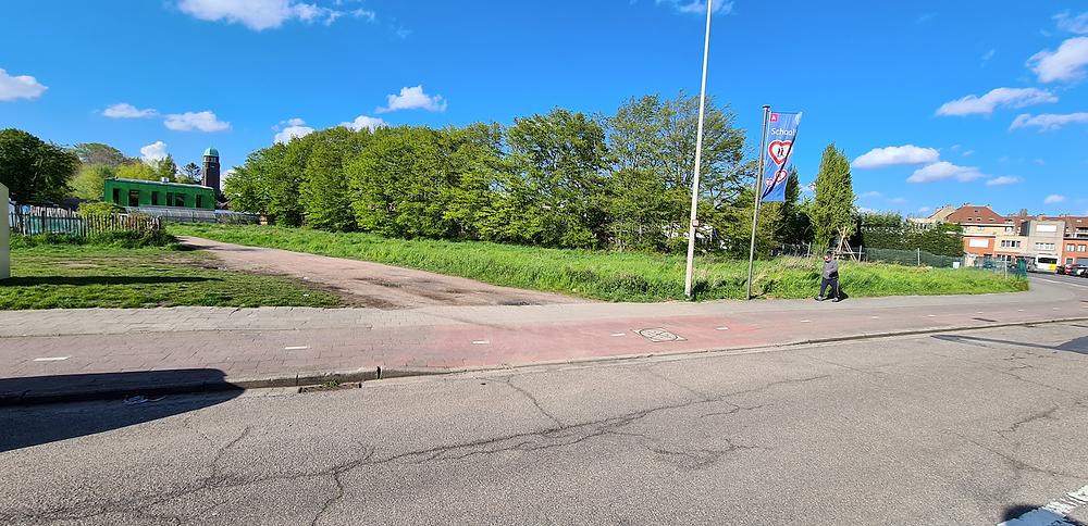 Drumul neasfaltat care ne duce din Dokter Veeckmanslaan către poarta școlii Rozenkrans. În fundal poate fi zărită turla bisericii noastre.