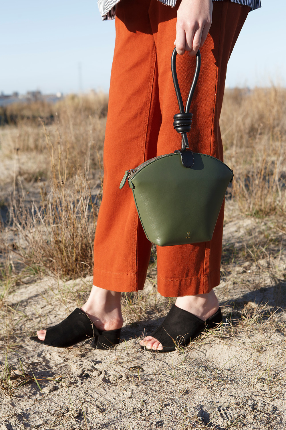 Editorial by Joko capturing leather bags by Dutch design label Ruigrok van der Werven. Featuring Jeanne at Touche model management. Jeanne wears blouse by Marni and trousers by Monki and shoes by Asos. Displaying Top handle bag Olive green / stone black