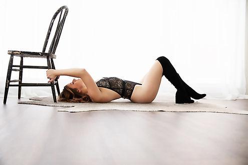 Wisconsin Minnesota Boudoir, woman in black lingerie lying on her back.