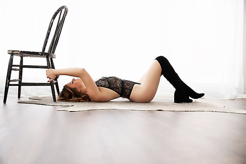 Wisconsin Minnesota Boudoir, woman in black lingerie lying on her back.