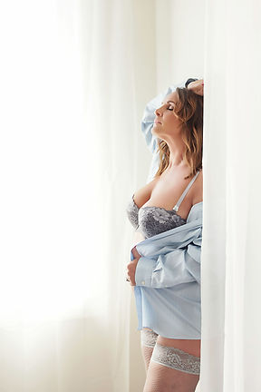 Boudoir photo of a woman in an unbuttoned shire and lingerie.