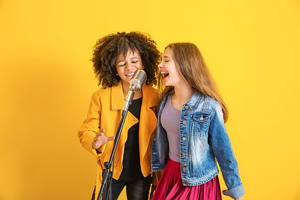 Teenage girls with microphone singing ag