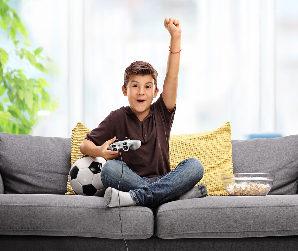 Boy playing console games such as FIFA 19
