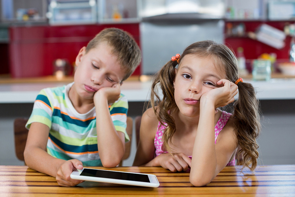 Bored children looking at a screen