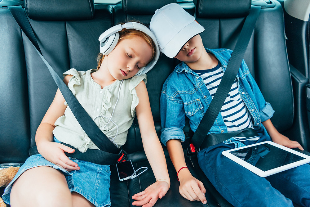 Bored kids listening to music in the car