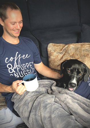 """""""coffee & pupper snuggles"""" navy tee worn by brown haired man smiling down at black and white dog in """"treatos & human snuggles"""" dog tee 