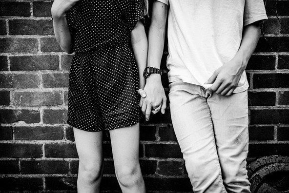 Black and white siblings holding hands.j