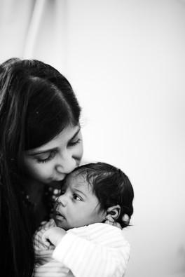 Mother kissing newborn on head.jpg