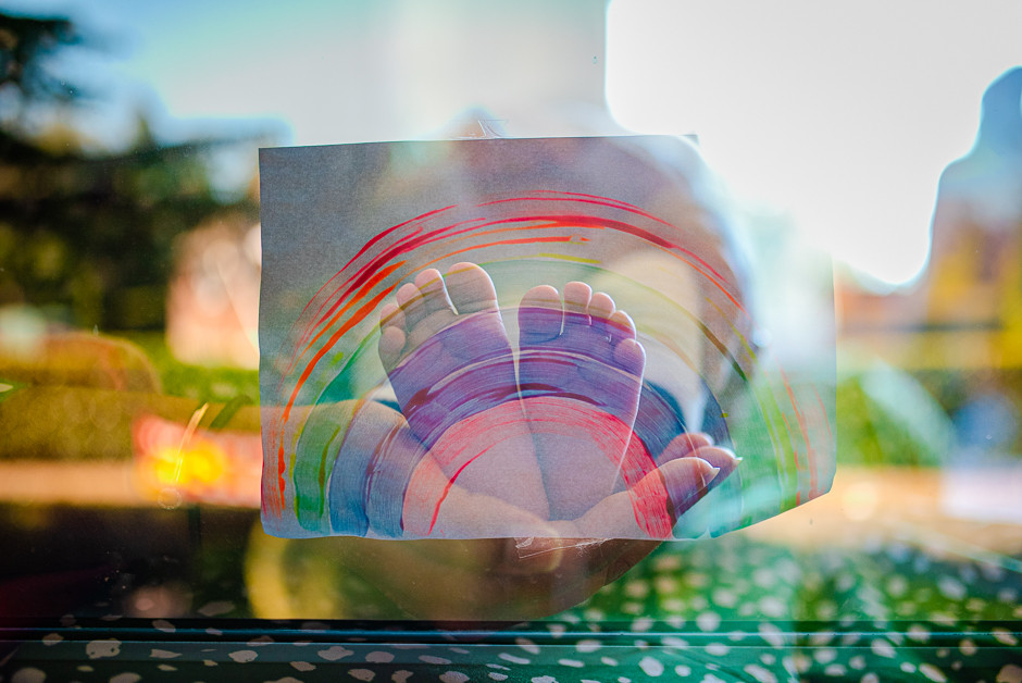 A double exposed photograph of baby feet being held with a child drawn rainbow