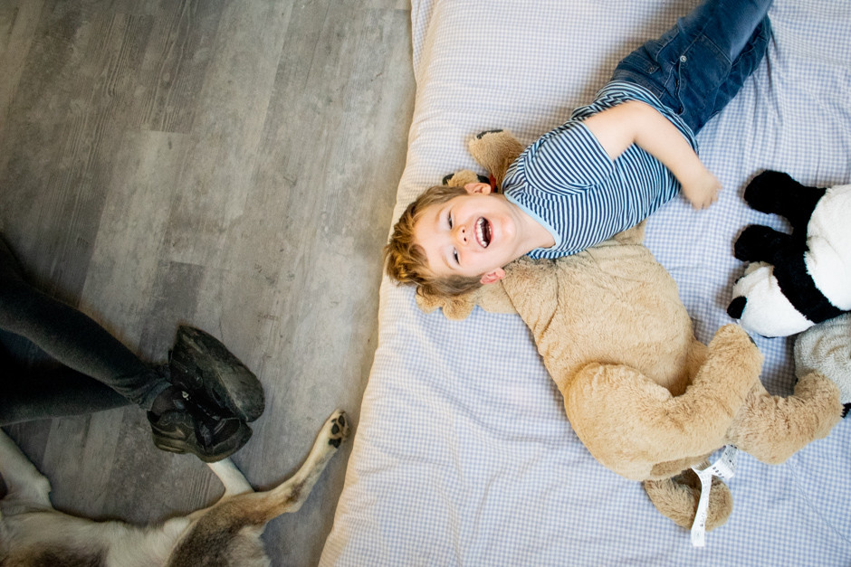Boy on bed in a in home family photography session. Woking family photography. Woking family photographer