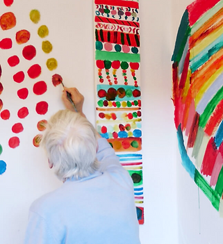 Helen Scott, Untitled, Gallery Space installation, Greenfield Park Care Home, 2013. A photograph of a woman painting directly onto white walls. She is painting quite abstract and very vivid patterns.