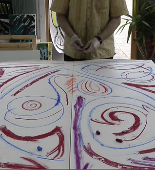 In the foreground we see large sheets of paper with abstract swirls and shaped in red, purple and orange. Behind this we can see a man with gloves on and the pastels in his hands.