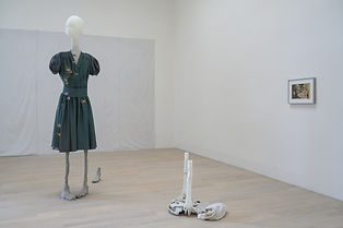 Cathy Wilkes Untitled, 2019 Mixed Media. A white walled gallery with installation: a small painting on the wall, mannequin-like sculpture wearing a dark green dress, with white head and spindly legs, a collection of objects on the floor.