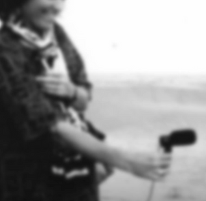 An out of focus black and white photograph. A cropped image of a woman smiling holding a microphone, pointing away from her body. It looks like a shoreline is visible in the distance.