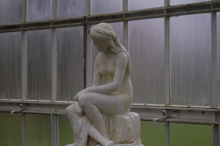 Colour photograph inside the Botanic Gardens glasshouse, with a white stone statue of a  sitting nude female with a headscarf.