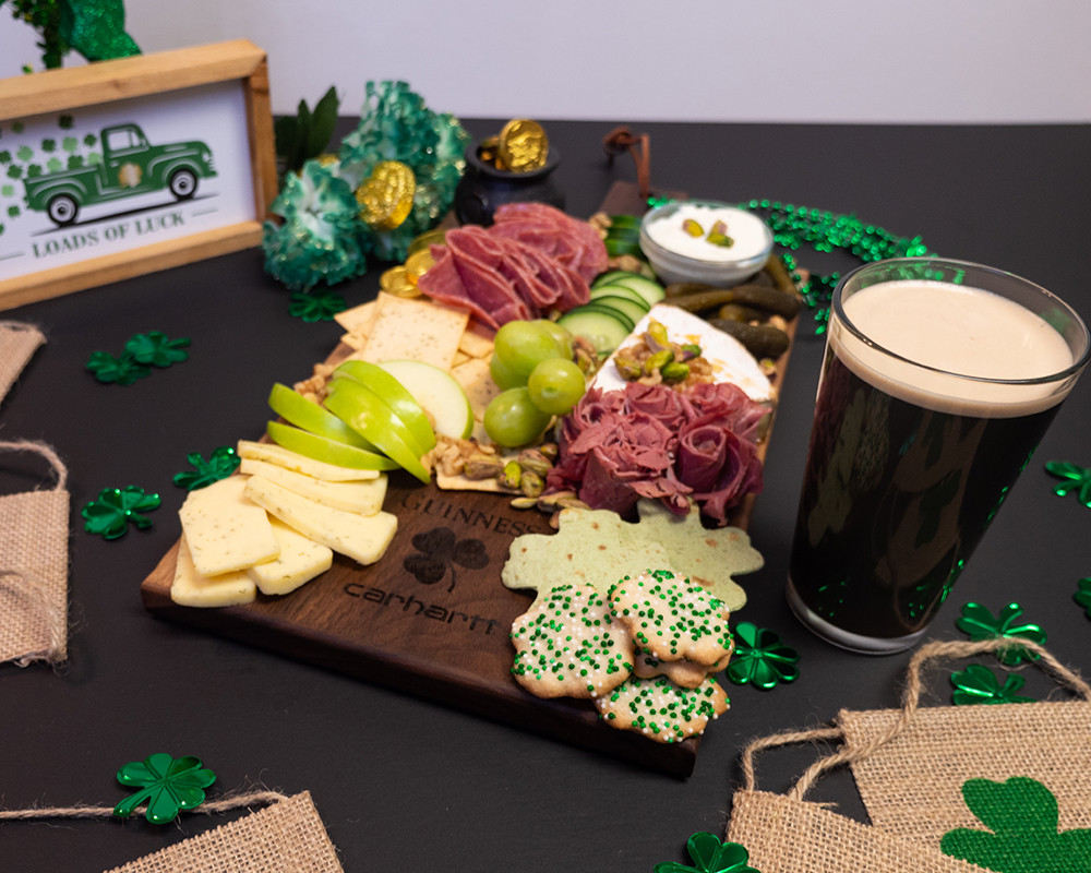 This is a St. Patrick's Day themed charcuterie board with the make your own parade campaign logo by Guinness and Carhartt engraved into it.