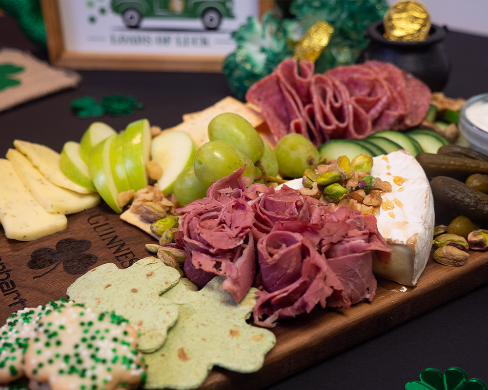 This is a solid walnut charcuterie board that has been decorated with St. Patrick's Day themed food.