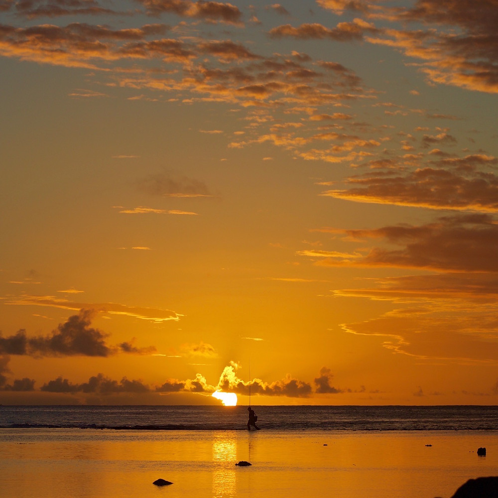 Fisherman on outer reef during sunset in Rarotonga, Cook Islands