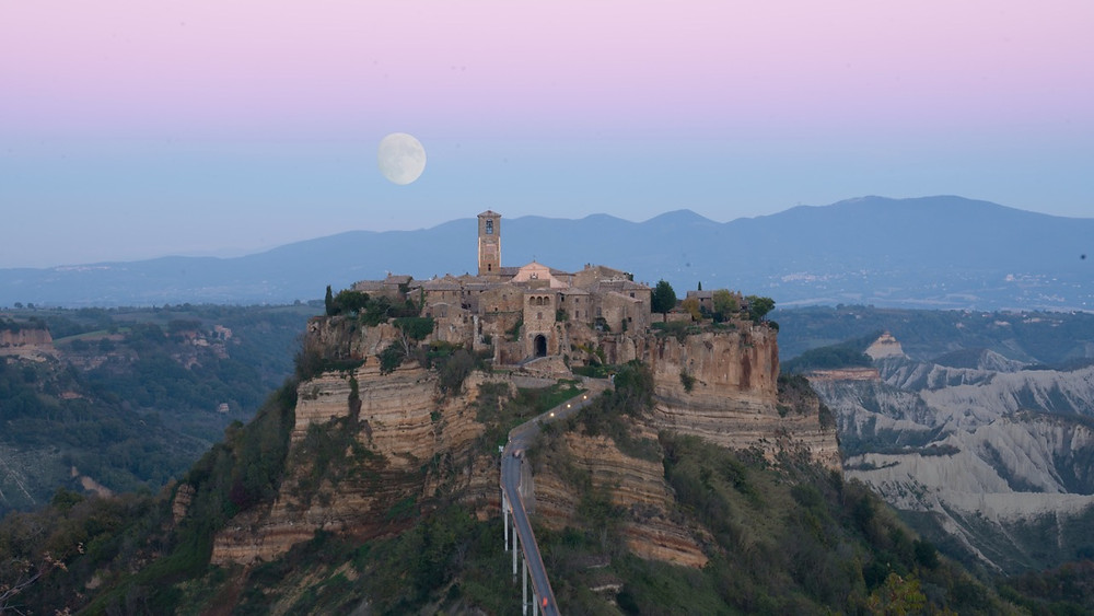 Moon rising above the medieval town of Bagnoregio in Italy