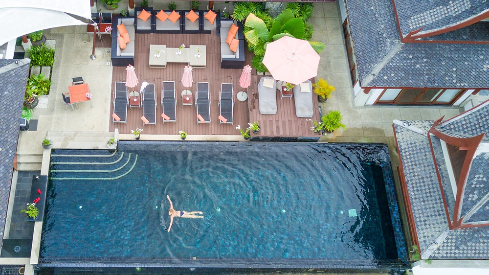 Woman swimming in rooftop pool in luxury thai villa Baan Phu Prana