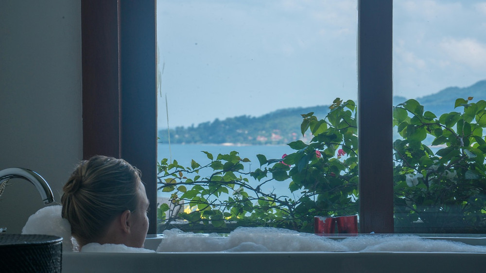 Woman in bath overlooking the ocean at Baan Phu Prana Villa