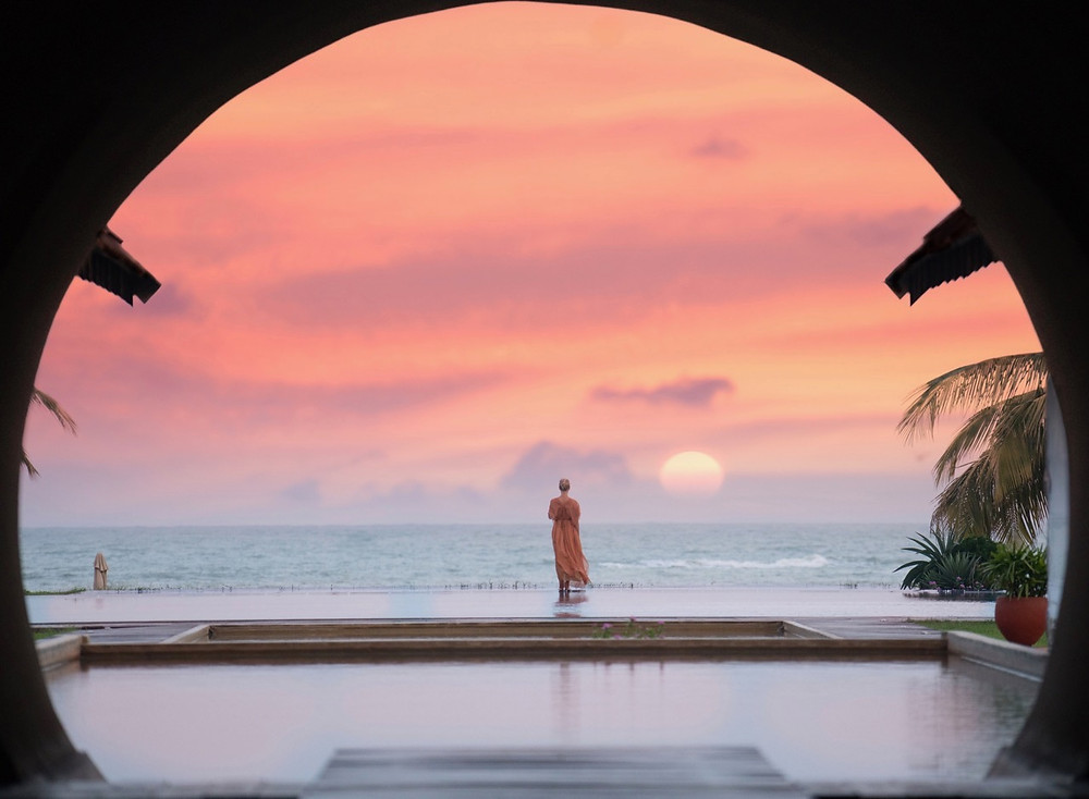 Pink sunrise over infinity pool and beach in northern Sri Lanka