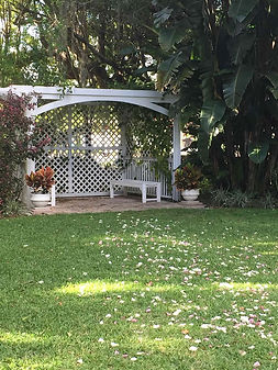 A beautful white gazebo with comfortable benches, lush trees, bushes, and flowers. Flower petals make a path from the green grass to the oasis of rest.