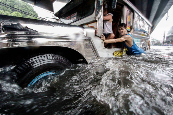 A man push a jeepney out of a flooded street during a heavy monsoon downpour in Manila, July 27, 2017.