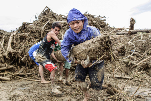 Villagers try to clear a debris in the Laor area in Nueva Ecija, Philippines on October 19, 2015. Thousands of people have been evacuated in the northern Philippines as Typhoon Koppu made landfall Sunday, destroying houses and knocking over trees and power lines.