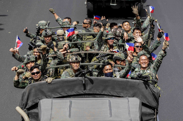After ending their deployment in Marawi City, Marine and Navy troops are welcomed as heroes as their truck passes along Roxas Boulevard in Manila in October.