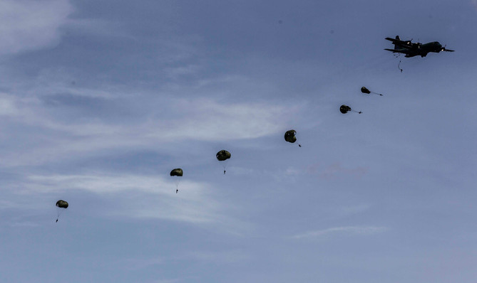 Philippine paratroopers drop from a C-130 transport plane during the Armed Forces of the Philippines 80th Anniversary celebration at Clark airbase in Angeles City, Pampanga province, December 21, 2015. The Armed Forces of the Philippines marked its 80th anniversary with a massive display of military assets, including its newly acquired South Korean made FA-50 jet fighter planes, combat helicopters, and various mobility assets.
