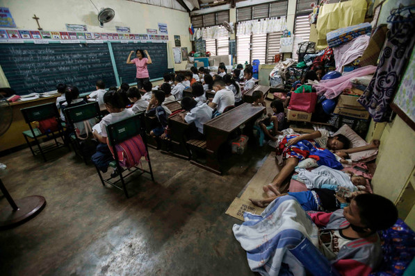 A teacher teaches pupils as evacuees take a rest at a evacuation center in Daraga,Albay, February 5,2018.