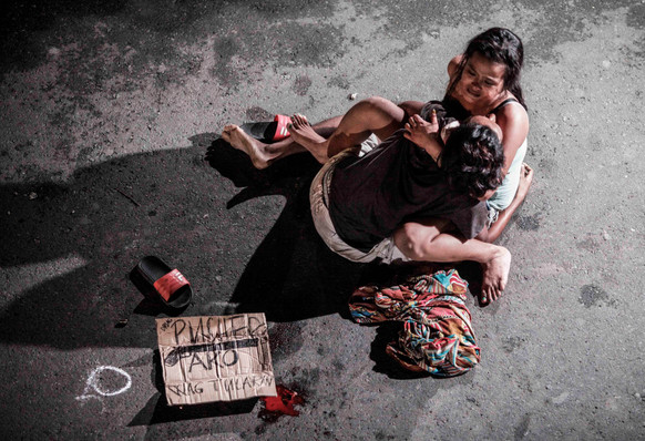 """A woman cradles the body of her husband, who was killed on a street by a vigilante group, according to police, in a spate of drug related killings in Pasay city, Metro Manila, Philippines July 23, 2016. A sign on a cardboard found near the body reads: """"Pusher Ako"""", which translates to """"I am a drug pusher""""."""