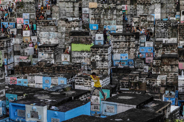 A boy leaps in-between apartment-style tombs as Filipinos visit the graves of their deceased loved ones to commemorate All Saints Day, at Barangka public cemetery in Marikina city, Metro Manila, Philippines November 1, 2016.