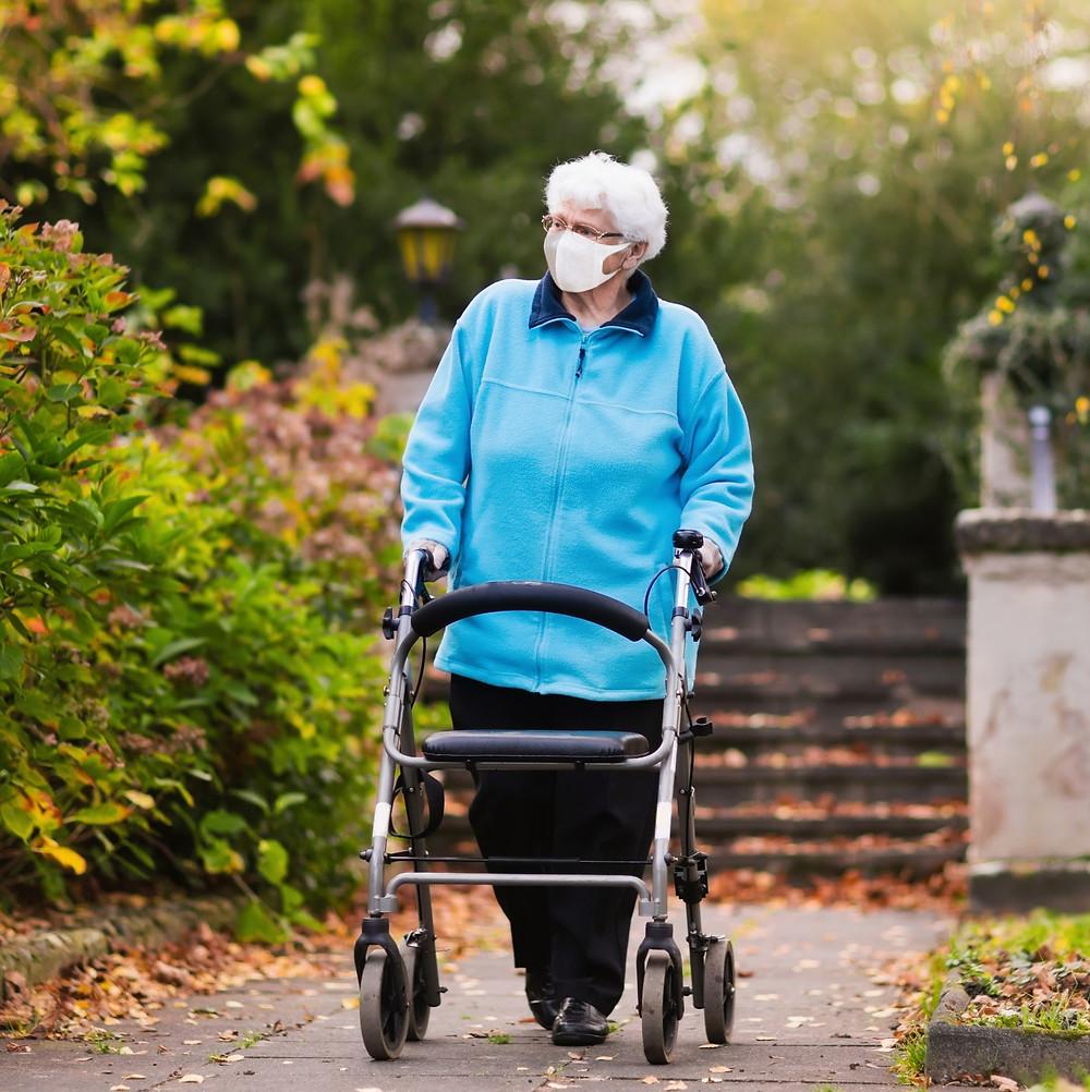 Senior woman walking with aid of walker