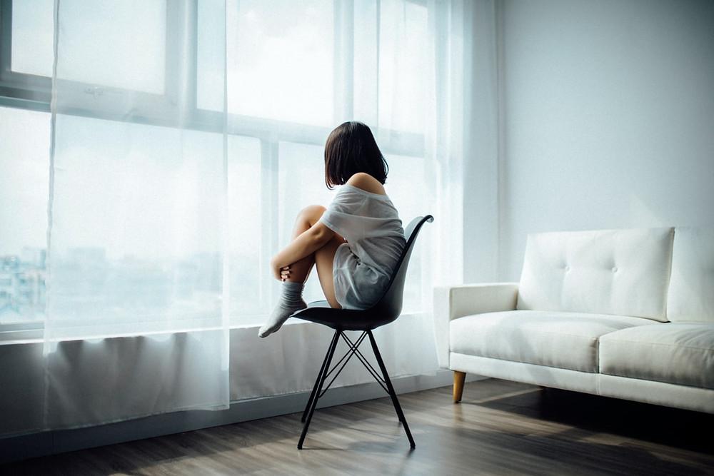 Moça sentada na cadeira olhando pela janela