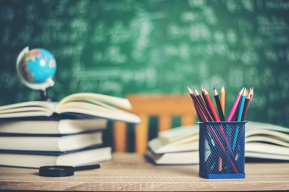Livros e pote com lápis em cima de uma mesa