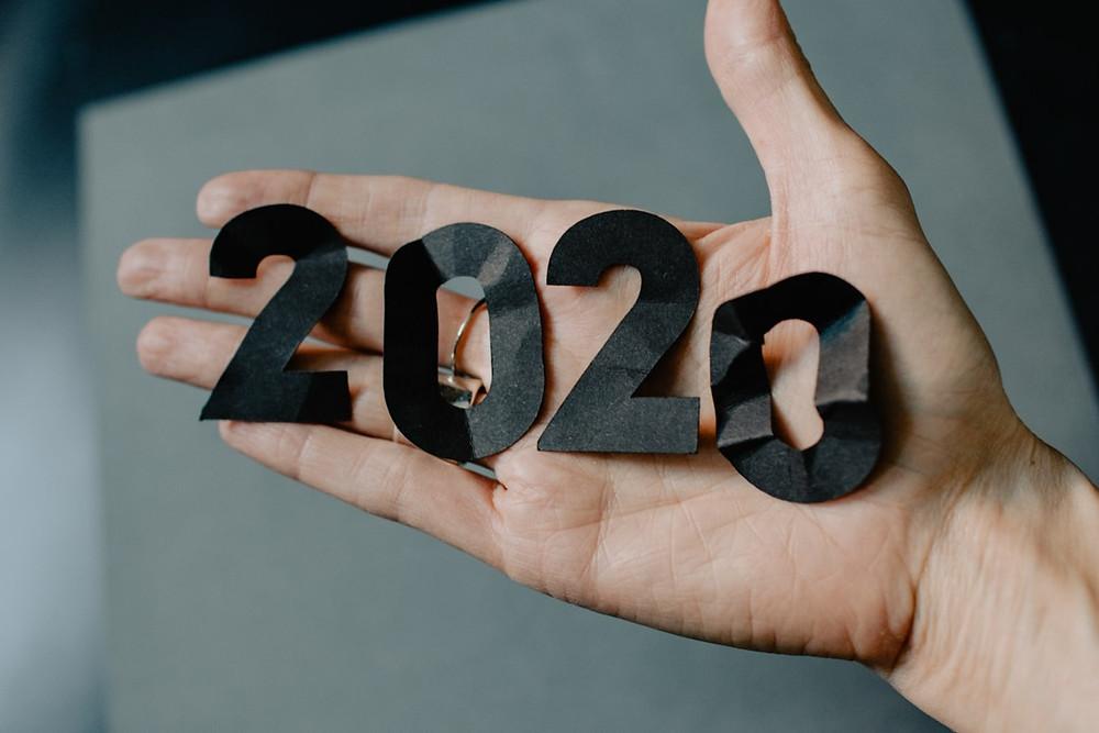 Mão segurando pedaços de papel que formam o número 2020