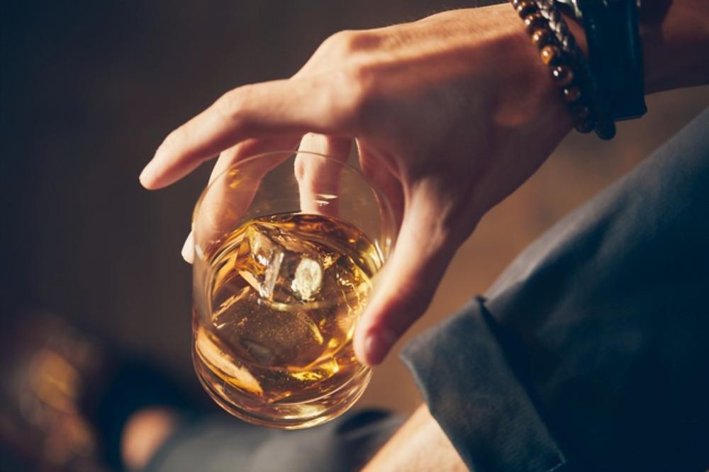 Homem segurando copo de whisky