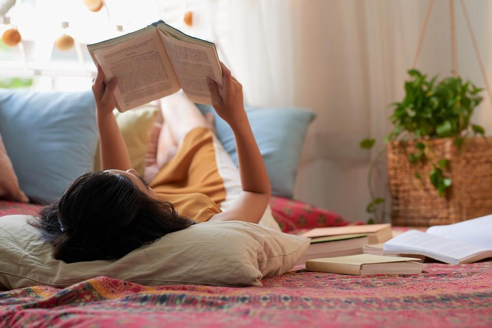 Menina deitada lendo um livro