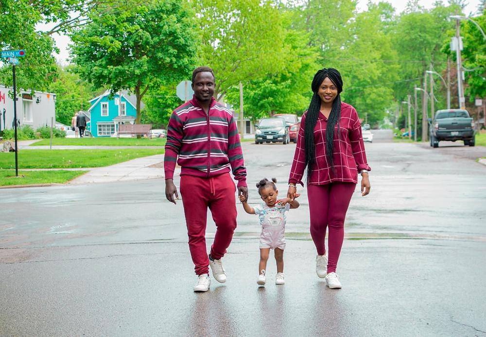 Pai, mãe e filha de mãos dadas passeando